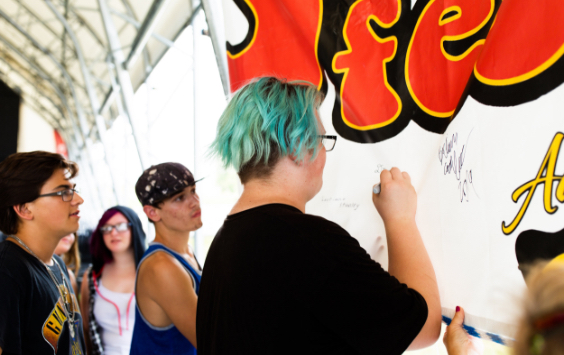 Audience members signing StonyFest banner